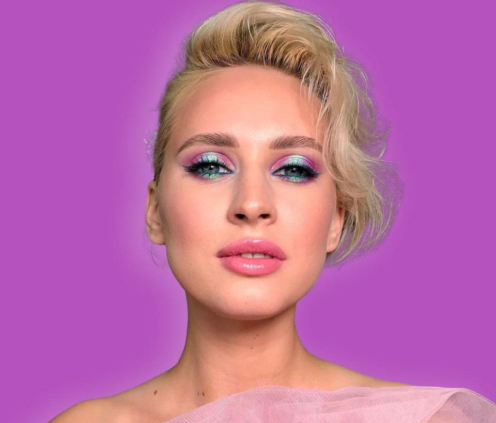 красивая девушка с макияжем на фиолетовом фоне